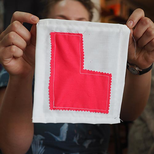 holding up a sewing L Plate